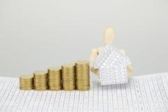 Hölzernes blindes haltenes Haus und Goldmünzen mit weißem Hintergrund Lizenzfreies Stockfoto