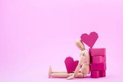 Hölzernes blindes und ein Stapel der roten Herzform des Papierkastens auf rosa BAC Lizenzfreies Stockbild