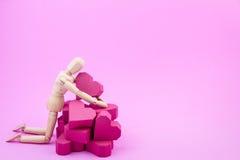 Hölzernes blindes und ein Stapel der roten Herzform des Papierkastens auf rosa BAC Stockbild