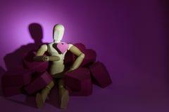 Hölzernes blindes und ein Stapel der roten Herzform des Papierkastens auf rosa BAC Lizenzfreie Stockfotografie