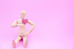 Hölzernes blindes und eine rote Herzform des Papierkastens auf rosa Hintergrund Stockbild