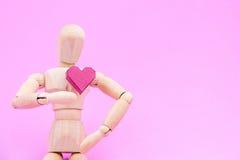 Hölzernes blindes und eine rote Herzform des Papierkastens auf rosa Hintergrund Stockfotos