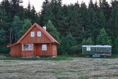 Hölzernes Blockhaus nahe Wald am bewölkten Tag und am beweglichen Transport Ca Lizenzfreies Stockbild
