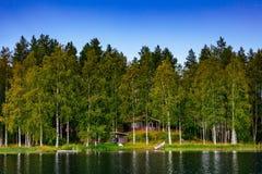 Hölzernes Blockhaus am See im Sommer in Finnland Stockfoto