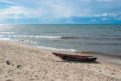 Hölzernes Boot auf dem sandigen Ufer vom Baikalsee, von blauem Himmel und von ruhigem Wasser lizenzfreies stockfoto