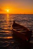 Hölzernes Boot auf dem See während des Sonnenuntergangs Lizenzfreie Stockbilder