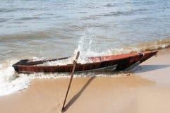 Hölzernes Boot auf dem Ufer vom Baikalsee und von Wasser spritzt stockbild