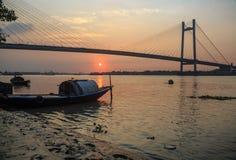 Hölzernes Boot auf Fluss Hooghly bei Sonnenuntergang mit der Vidyasagar-Brücke am Hintergrund Stockbilder