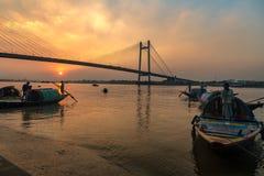 Hölzernes Boot auf Fluss Hooghly bei Sonnenuntergang mit Vidyasagar-Brücke am Hintergrund Stockfoto