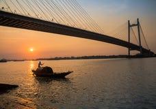Hölzernes Boot auf Fluss Hooghly bei Sonnenuntergang mit Vidyasagar-Brücke am Hintergrund u. am x28; silhouette& x29; Kolkata, In lizenzfreies stockbild