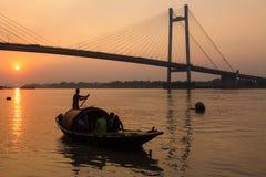 Hölzernes Boot auf Fluss Hooghly bei Sonnenuntergang nahe Vidyasagar-Brücke Lizenzfreies Stockfoto