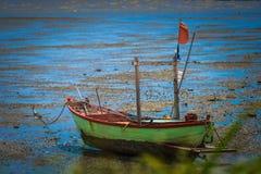 Hölzernes Boot in der Ebbe, die aus den Grund legt lizenzfreies stockbild