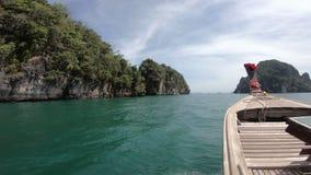 hölzernes Boot des langen Schwanzes 4K auf den Wellen mit Insel bei Thailand stock video