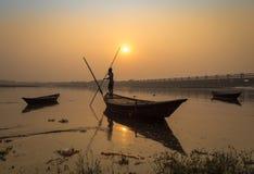 Hölzernes Boot mit Ruderer bei Sonnenuntergang auf Fluss Damodar, nahe Durgapur-Damm Stockfoto