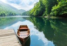 Hölzernes Boot am Pier auf Gebirgssee Stockfotos