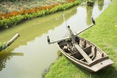 Hölzernes Boot und Maschine für die Bewässerung zur Anlage und zum Gemüse im Garten Stockfotografie