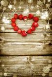 Hölzernes Brett des alten Schmutzes mit Glühlampegrenze, Erdbeere in Form eines Herzens Lizenzfreie Stockfotos
