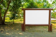 Hölzernes Brett im Allgemeinen Park mit grünem Baumhintergrund Lizenzfreies Stockbild