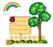 Hölzernes Brett im Garten mit Baum und Regenbogen Lizenzfreies Stockfoto