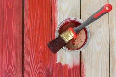 Hölzernes Brett mit einer Dose Farbe an der Malerei stockbild