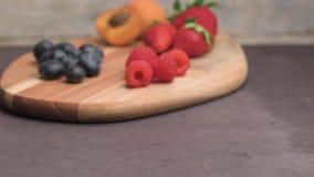 Hölzernes Brett mit frischer organischer Frucht und Beeren stock video