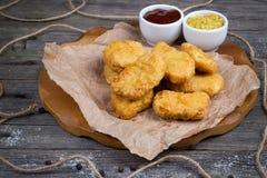 Hölzernes Brett mit geschmackvollen Hühnernuggets und -soßen Stockfotos