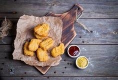 Hölzernes Brett mit geschmackvollen Hühnernuggets und -soßen auf Tabelle Lizenzfreie Stockfotos