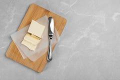 Hölzernes Brett mit geschmackvoller frischer Butter und Messer Lizenzfreies Stockfoto