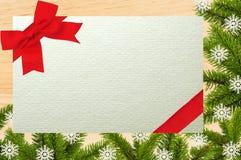 Hölzernes Brett mit grünem Weihnachtsbaumast und Grußkarte Stockbild