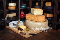 Hölzernes Brett mit verschiedenen Arten des köstlichen Käses auf Tabelle lizenzfreies stockfoto
