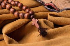 Hölzernes christliches Kreuz und Rosenbeet und alte Bibel auf einem Hintergrund des goldenen Gewebedrapierung Lizenzfreies Stockfoto