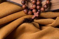 Hölzernes christliches Kreuz und Rosenbeet und alte Bibel auf einem Hintergrund des goldenen Gewebedrapierung Stockfoto