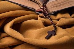 Hölzernes christliches Kreuz und Rosenbeet und alte Bibel auf goldenem Gewebedrapierung Heilige Schrift Stockfotografie