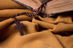 Hölzernes christliches Kreuz und Rosenbeet und alte Bibel auf goldenem Gewebedrapierung Heilige Schrift Stockfoto