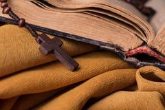 Hölzernes christliches Kreuz und Rosenbeet und alte Bibel auf goldenem Gewebedrapierung Heilige Schrift Lizenzfreie Stockfotos