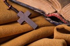 Hölzernes christliches Kreuz und Rosenbeet und alte Bibel auf goldenem Gewebedrapierung Heilige Schrift Stockfotos