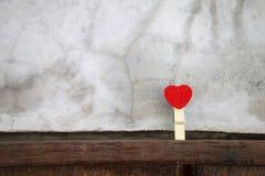 Hölzernes Clip des roten Herzens mit Raum auf grauem Zementwandhintergrund stockbilder