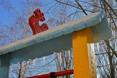 Hölzernes Dach und Eiszapfen auf dem Winterspielplatz Lizenzfreies Stockfoto