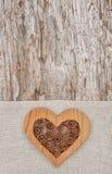 Hölzernes dekoratives Herz auf dem Leinengewebe und dem alten Holz Stockbilder