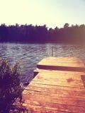 Hölzernes Dock auf Banken von See oder von Fluss Stockbild
