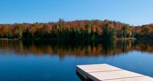 Hölzernes Dock auf Herbstsee Stockfotografie