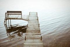 Hölzernes Dock, das in das Wasser führt Stockfotos