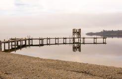 Hölzernes Dock mit Ufer während der Wintersaison stockfotografie
