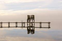 Hölzernes Dock mitten in dem Wasser während Wint stockbild