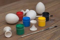 Hölzernes Ei auf dem Tisch neben den Farben und den Bürsten Stockbilder