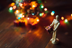 Hölzernes eingehängtes Mannequin mit dem Geschenk und dem Chritsmas-Baum Lizenzfreies Stockfoto