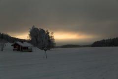 Hölzernes einsames Haus im Schneetal auf Sonnenunterganghintergrund in Levi, Finnland Stockfotografie