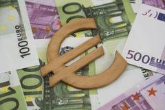 Hölzernes Eurozeichensymbol auf einen und fünfhundert Eurobanknoten Stockfoto