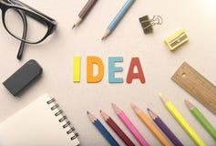 Hölzernes Farbalphabet mit Ideenwort und Glühlampe auf Tabelle Stockfotos