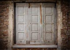 Hölzernes Fenster auf Backsteinmauer Stockbild